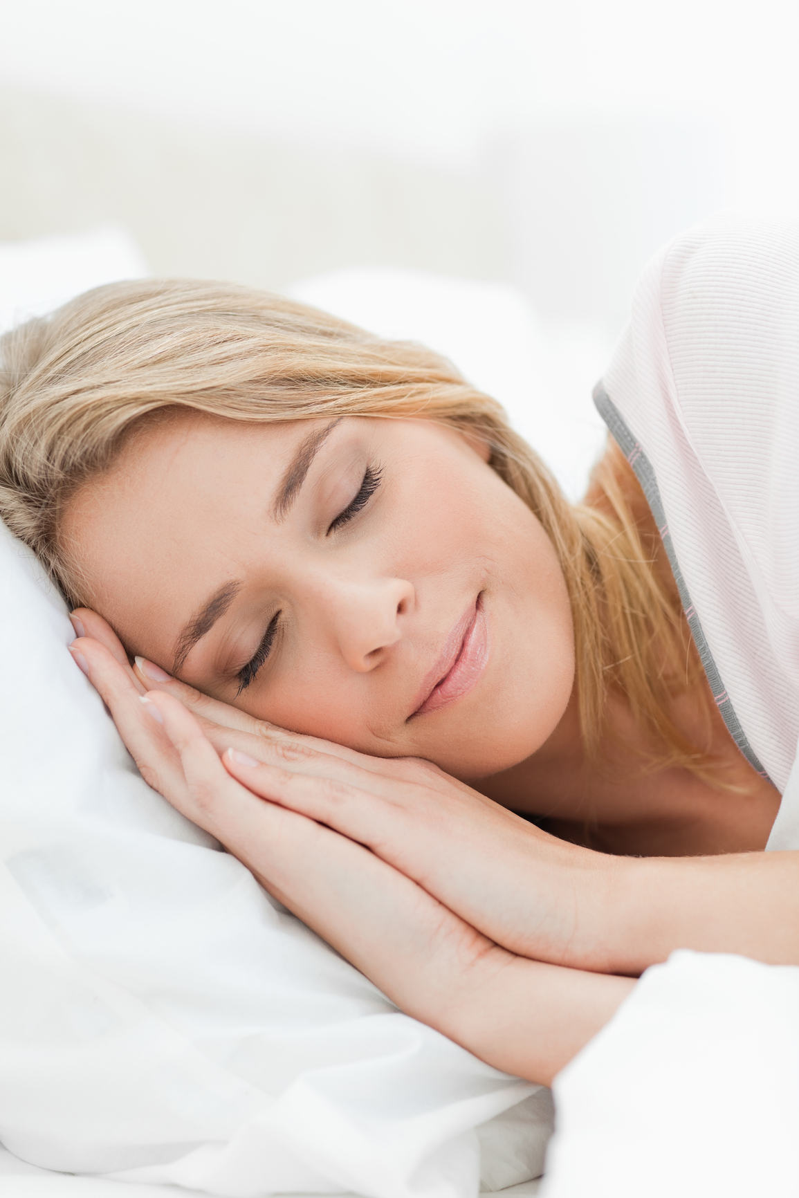Close up, woman asleep with hands beside her head resting on a pillow